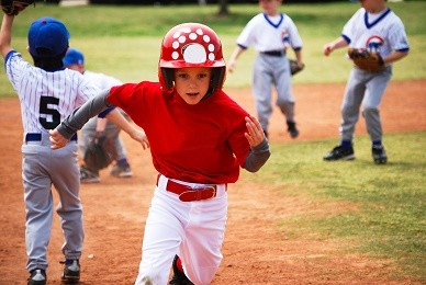 Little league baseball player running bases